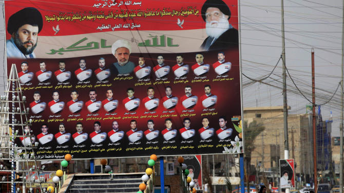 "In this Sunday, Feb. 24, 2013 photo, Iraqi women walk past a billboard showing Shiite religious leaders and Shiite's who were killed during a fight between US troops and al-Mahdi Army militia in the Jihad neighborhood of west Baghdad, Iraq. The fliers claiming to be from a new Iranian-linked Shiite militant group began turning up last week in front of Iraqi Sunni households bearing a chilling message: Get out now or face ""great agony"" soon.   (AP Photo/ Karim Kadim)"