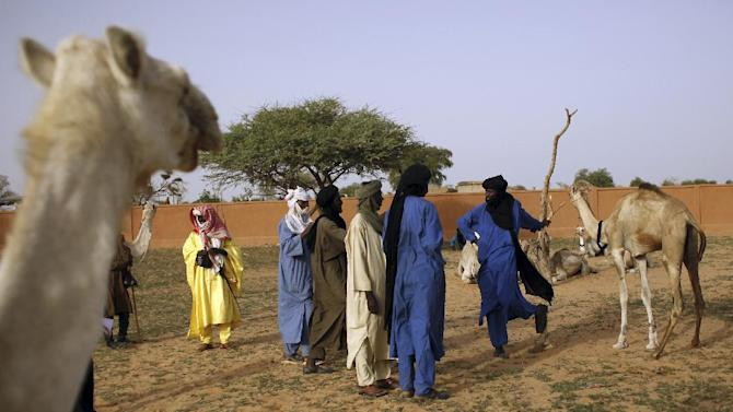 In this picture taken Sunday, July 22, 2012, Tuareg men negotiate the sale of camels at the livestock market in the desert village of Sakabal, Niger, 220 kms (140 miles)  north of Maradi. Eighty percent of Niger's people and 100 percent of the landlocked nation's rural population depend on livestock, including camel, cows, sheep and goats, for some part of their income. For generations, nomads have lived in a precarious equilibrium with the sky above them. When the first rains come, they head north toward the Sahara desert, where the grass is said to be saltier, packed with minerals. They time their movements according to the clouds, waiting for the second major downpour, before making a U-turn to head back to the greener south. If they miscalculate, they can end up stranded. As the grass turns yellow, their animals become too weak to walk. (AP Photo/Jerome Delay)