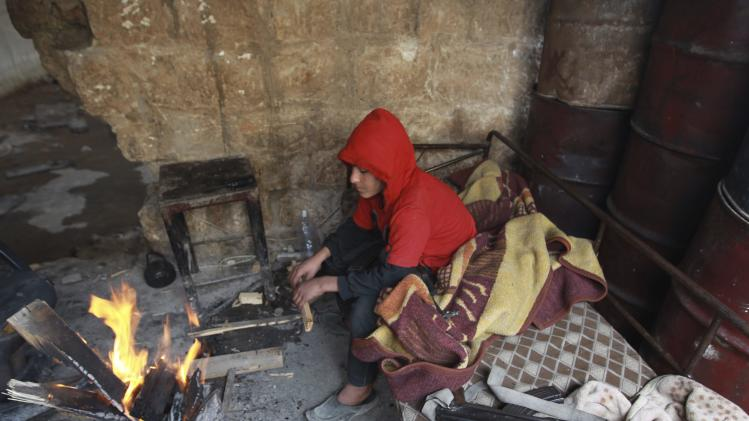 Noor rests by a fire at the frontline of Khalidiya neighborhood in Aleppo