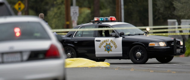 A body lays in the intersection of Wanda Road and Katella Avenue early Tuesday, Feb. 19, 2013 in Orange County, Calif.,  as local police agencies investigate the scene.  Police say a chaotic 25-minute