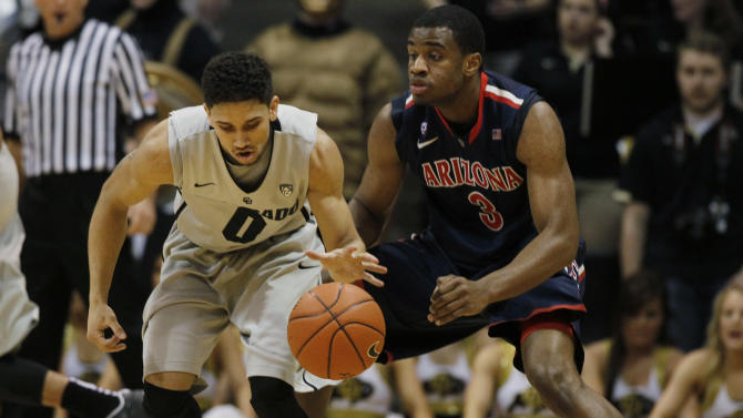 Colorado guard Askia Booker, left, picks up a loose ball as Arizona guard Kevin Parrom covers in the first half of an NCAA college basketball game in Boulder, Colo., Thursday, Feb. 14, 2013. (AP Photo/David Zalubowski)
