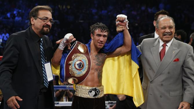 Lomachenko of Ukraine celebrates his victory over Chonlatarn of Thailand during their WBO 12-round featherweight title fight at the Venetian Macao hotel in Macau