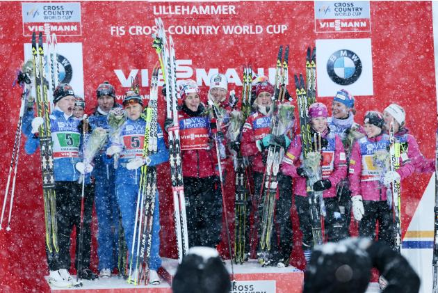 Team Finland, team Norway and team USA celebrate on the podium after the women's 4x5 km relay at the FIS Cross-Country World Cup in Lillehammer