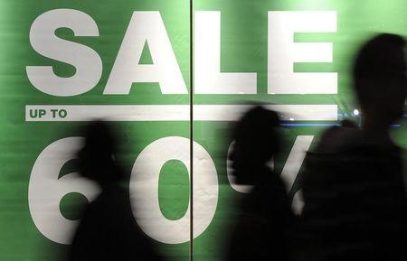 Shoppers walk past a sale sign on Oxford Street in central London