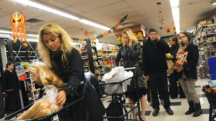 Gozde Guldosuren stocks up on bread at a Manhattan grocery store, Sunday, Oct. 28, 2012, in New York. Tens of thousands of people were ordered to evacuate coastal areas Sunday as big cities and small towns across the U.S. Northeast braced for the onslaught of a superstorm threatening some 60 million people along the most heavily populated corridor in the nation. (AP Photo/ Louis Lanzano)