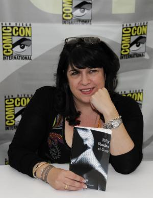 """Author E.L. James poses with her book """"Fifty Shades of Grey"""" at a book signing during the first day of Comic-Con convention held at the San Diego Convention Center on Thursday July 12, 2012, in San Diego.  (Photo by Denis Poroy/Invision/AP)"""