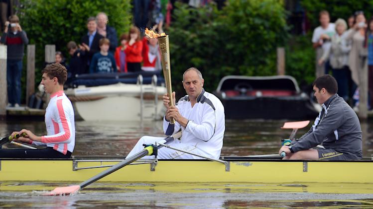 This image made available by LOCOG shows former Olympic gold medalist and torchbearer 030 Sir Steve Redgrave carrying the Olympic Flame on a boat on the River Thames on the Torch Relay leg between Wallingford and Henley on Thames, England, Tuesday July 10, 2012. (AP Photo/Joe Giddens, LOCOG)