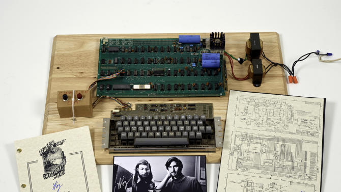 """This undated photo provided by Christie's Auction House shows an """"Apple 1"""" prototype computer, built in 1976, accompanied by an operation manual and schematic as well as a photo of its inventors, Steve Wozniak, left, and Steve Jobs. One of the very first Apple 1 computers, it goes on sale later this month at Christie's auction house, the latest in a recent run of vintage tech sales that have attracted some eye-popping prices. (AP Photo/Christies Images Ltd. 2013)"""