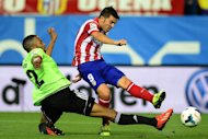 Atletico Madrid's David Villa (R) shoots past a tackle attempt from Osasuna defender Jordan Loties during their Spanish league match at the Vicente Calderon stadium in Madrid on September 24, 2013