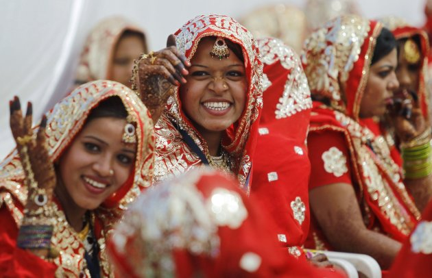 Muslim brides smile as they wait for the start of their rituals during a mass marriage ceremony in Ahmedabad