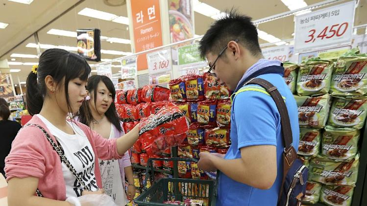 """In this Aug. 18. 2014 photo, customers pick up a package of """"ramyeon"""" instant noodles in a basket at a shopping center in Seoul, South Korea. By value, instant noodles were the top-selling manufactured food in South Korea in 2012, the most recent year figures are available, according to South Korea's Ministry of Food and Drug Safety. The country sold about 1.85 trillion won ($1.8 billion) worth, mostly in domestic markets, that year. (AP Photo/Ahn Young-joon)"""