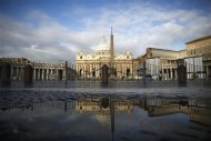 Saint Peter's Basilica is reflected in a puddle near the Vatican, March 11, 2013. REUTERS/Paul Hanna