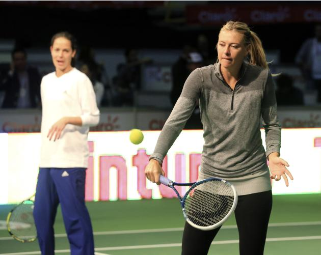 Maria Sharapova of Russia and Ana Ivanovic of Serbia return a ball to a group of young players during a training clinic in Bogota