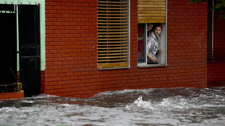 A couple looks at their flooded street from behind their home's window in La Plata, in Argentina's Buenos Aires province, Wednesday, April 3, 2013. At least 35 people were killed by flooding overnight in Argentina's Buenos Aires province, the governor said Wednesday, bringing the overall death toll from days of torrential rains to at least 41 and leaving large stretches of the provincial capital under water. (AP Photo/Natacha Pisarenko)