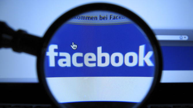 FILE - In this Oct. 10, 2011 file photo, a magnifying glass is posed over a monitor displaying a Facebook page in Munich. Facebook is proposing to end its practice of letting users vote on changes to its privacy policies, though it will continue to let users comment on proposed updates. The world's biggest social media company said in a blog post Wednesday, Nov. 21, 2012, that its voting mechanism, which is triggered only if enough people comment on proposed changes, has become a system that emphasizes quantity of responses over quality of discussion. Users tend to leave one or two-word comments objecting to changes instead of more in-depth responses. (AP Photo/dapd, Joerg Koch, File)