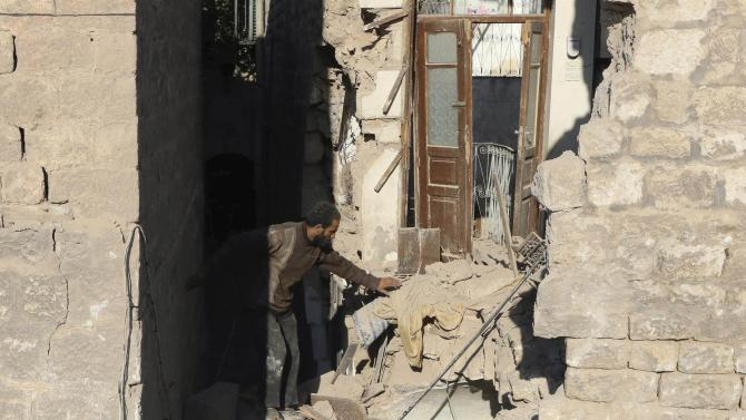 A man inspects his damaged house at a site hit by what activists said was a barrel bomb dropped by forces loyal to Syria's President Bashar Al-Assad in Bab al-Hadeed neighbourhood in the old city of Aleppo