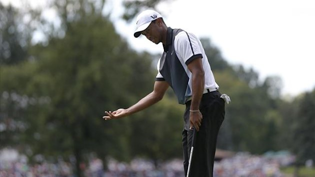 Tiger Woods reacts after missing a birdie putt on the fourth green during the third round of the 2013 PGA Championship golf tournament at Oak Hill Country Club in Rochester, New York August 10, 2013 (Reuters)
