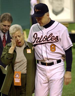 FILE - This Oct. 6, 2001 file photo shows Cal Ripken escorting his mother, Vi, from the field, after throwing out the ceremonial first pitch before Cal's final game, at Oriole Park in Baltimore. Police say Cal Ripken Jr.'s mother is safe after an armed man abducted her from her home northeast of Baltimore. Aberdeen police say 74-year-old Vi Ripken was kidnapped between 7 a.m. and 8 a.m. Tuesday, July 24, 2012,  by a man who forced her into her car. (AP Photo/Nick Wass)