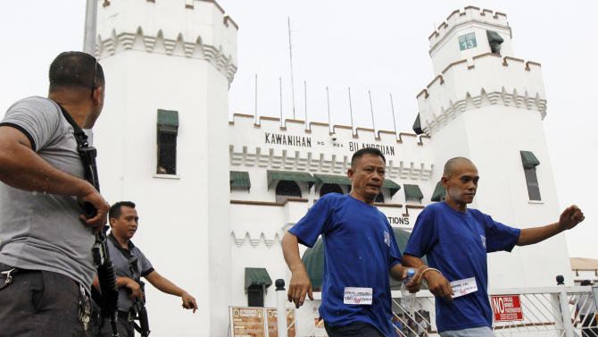 Inmates in handcuffs at the National Penitentiary are escorted to vote at a polling precinct inside the prison compound for the country's midterm elections at Muntinlupa city, south of Manila, Philippines Monday, May 13, 2013. More than 50 million Filipinos are expected to troop to polling centers to elect senators, congressmen and down to municipal mayors for the country's midterm elections. More than 2,000 prisoners were allowed to participate in the country's electoral process. (AP Photo)