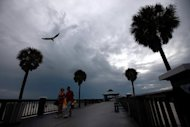 Visitors walk along the Clearwater Pier as storms build offshore in Clearwater, Florida. A strengthening Tropical Storm Isaac is barreling toward Florida and is predicted to become a hurricane on Sunday, forcing a one-day delay to the main events of the Republican convention, after leaving four people dead in Haiti