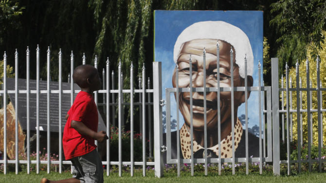 A child runs past a large portrait of former president Nelson Mandela in a Soweto park Sunday, Dec. 16, 2012. Mandela underwent a successful surgery to remove gallstones Saturday, the nation's presidency said, as the 94-year-old anti-apartheid icon is still recovering from a lung infection. Doctors treating Mandela waited to perform the endoscopic surgery as they wanted to first attend to his lung ailment, presidential spokesman Mac Maharaj said in a statement. Mandela has been hospitalized since Dec. 8. (AP Photo/Denis Farrell)