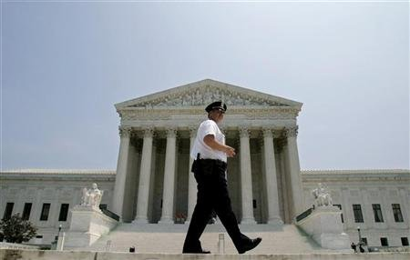 Police officer patrols outside US Supreme Court in Washington after Justice O'Connor announced her resignation. REUTERS/Shaun Heasley