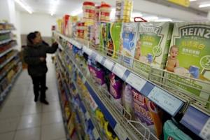 Chinese customers select food on a shelf where Heinz products are displayed in a market in Shanghai