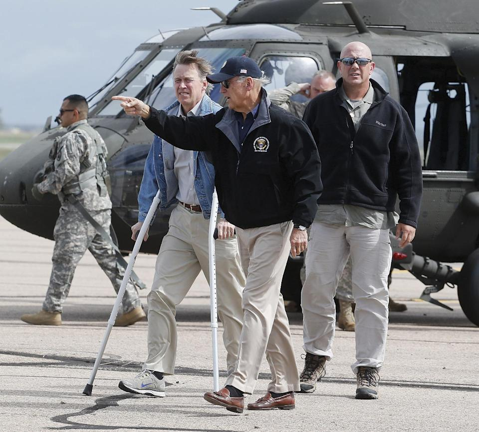 Vice President Joe Biden leads Colorado Gov. John Hickenlooper, left, from a helicopter after landing in Greeley, Colo., Monday, Sept. 23, 2013. Biden, Hickenlooper and other officials took a tour of the flood stricken areas of the state. (AP Photo/Ed Andrieski)