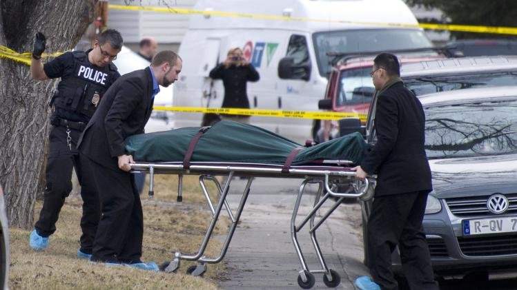 Police remove a body from the scene of a multiple fatal stabbing in northwest Calgary, Alberta, Tuesday, April 15, 2014. Police say five people are dead after the stabbing at a house party. (AP Photo/The Canadian Press, Larry MacDougal)