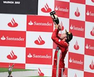 Ferrari's Spanish driver Fernando Alonso celebrates on the podium at the Valencia Street Circuit in Valencia after the European Formula One Grand Prix