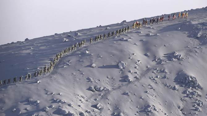 In this Oct. 1, 2014 photo, rescuers walk in line after their search operation near the peak of Mount Ontake in central Japan. Saturday's eruption on Mount Ontake was the worst fatal eruption in postwar history in Japan. (AP Photo/Mainichi Shimbun, Kimi Takeuchi) MANDATORY CREDIT, JAPAN OUT, NO SALES,