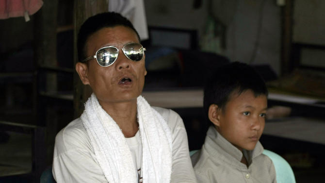 In this photo taken April 12, 2013, Saw Pa Taw, left, a former Karen fighter who lost both his eyes and hands, during fighting with Myanmar soldiers talks as and son Ta Ye Thu, 13, listens during an interview at Mae La refugee camp in Ta Song Yang district of Tak province, northern Thailand. Karen refugees are now facin a future that will dramatically change their constricted but secure, sometimes happy lives. With the end of 50 years of military rule in Myanmar, aid groups are beginning to prepare for the eventual return of one of the world's largest refugee populations, some 1 million in camps and hideouts spread across five countries. (AP Photo/Apichart Weerawong)