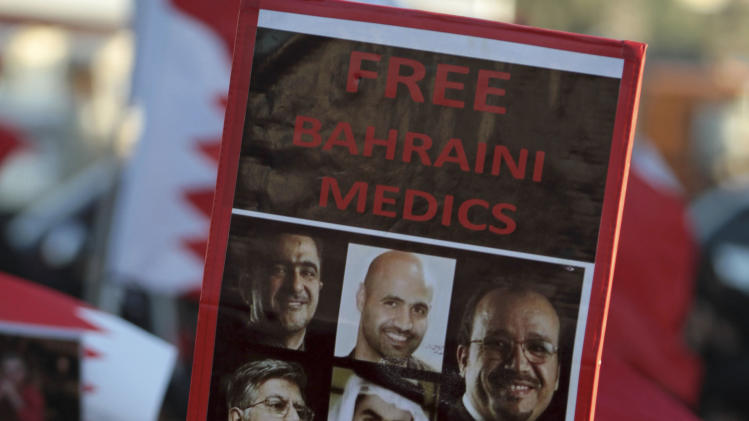 "Senior nurse Rula al Saffar carries a sign with images of jailed Bahraini medics during an anti-government march Sunday, Feb. 3, 2013, in the western village of Malkiya, Bahrain. Hundreds shouted ""down with the government"" during the march which was called by several opposition groups to demand freedom for political prisoners and democracy in the Gulf island kingdom. (AP Photo/Hasan Jamali)"