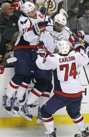 Washington Capitals right wing Joel Ward, center, is congratulated by teammates after his goal against the Boston Bruins during overtime of Game 7 of an NHL hockey Stanley Cup first-round playoff series, in Boston on Wednesday, April 25, 2012. The Capitals won 2-1. From left with Ward are Karl Alzner and John Carlson. (AP Photo/Charles Krupa)