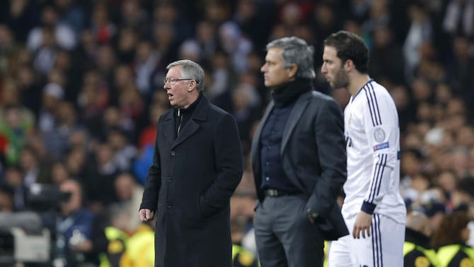 Manchester United's manager Sir Alex Ferguson, left, is seen along with Real Madrid's coach Jose Mourinho from Portugal, center and Gonzalo Higuain from Argentina, during the Champions League round of 16 first leg soccer match between Real Madrid and Manchester United at the Santiago Bernabeu stadium in Madrid, Wednesday Feb. 13, 2013. (AP Photo/Daniel Ochoa de Olza)