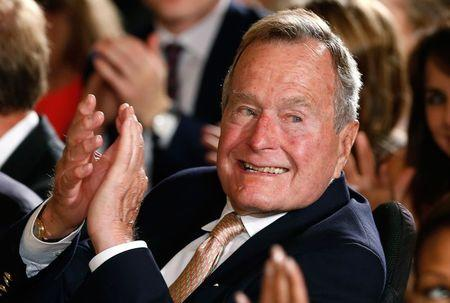 Former President George H. W. Bush applauds during an event to honor the winner of the 5,000th Daily Point of Light Award at the White House in Washington in this file photo