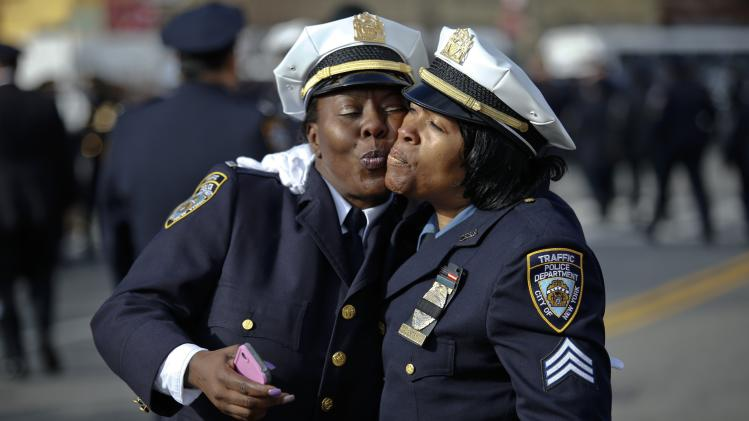 NYPD Traffic Enforcement Agents kiss each other while attending the funeral service of Ranasinghe in New York