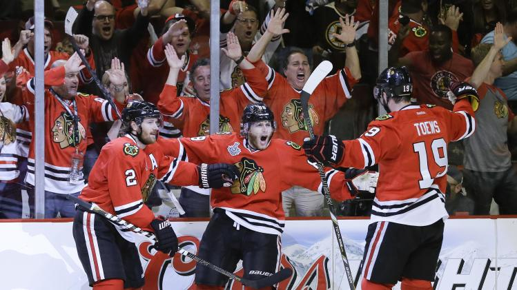 Chicago Blackhawks right wing Patrick Kane (88) celebrates with center Jonathan Toews (19) and defenseman Duncan Keith (2) after scoring a goal against the Boston Bruins in the second period during Game 5 of the NHL hockey Stanley Cup Finals, Saturday, June 22, 2013, in Chicago. (AP Photo/Nam Y. Huh)