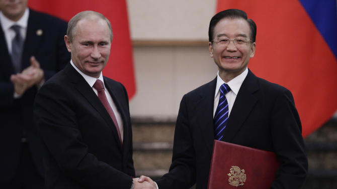 Russia's Prime Minister Vladimir Putin, left, shakes hands with China's Premier Wen Jiabao during a signing ceremony at the Great Hall of the People in Beijing, China on Tuesday Oct. 11, 2011. (AP Photo/Jason Lee, Pool)