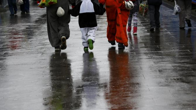 Carnival revellers walk along wet street after Rosenmontag parade cancelled in Mainz