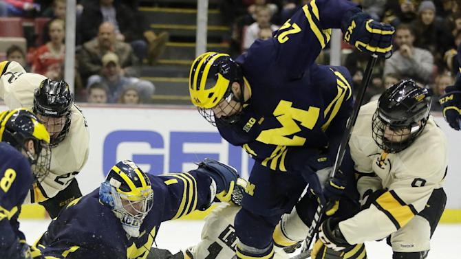 Michigan's Kevin Lohan (24) tries to clear the puck after goalie Steve Racine (1) stopped a shot by Michigan Tech's Alex Gillies, right, during the second period of the Great Lakes Invitational NCAA college hockey game, Sunday, Dec. 28, 2014, in Detroit. (AP Photo/Duane Burleson)
