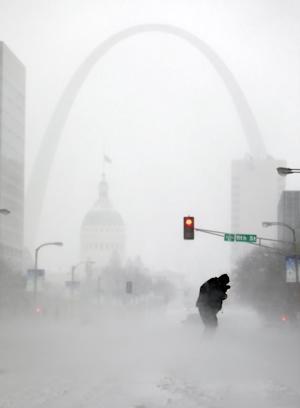 FILE - In this Sunday, Jan. 5, 2014, file photo, a person struggles to cross a street in blowing and falling snow as the Gateway Arch appears in the distance, in St. Louis. The deep freeze that gripped much of the nation this week wasn't unprecedented, but with global warming we're getting far fewer bitter cold spells, and many of us have forgotten how frigid winter used to be. (AP Photo/Jeff Roberson, File)
