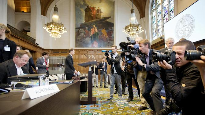 Photographers take pictures of the Australian delegation with General Counsel of Australia Bill Campbell, left, at the International Court of Justice (ICJ) in The Hague, Netherlands, Wednesday, June 26, 2013. Australia is urging the United Nations' highest court to ban Japan's annual whale hunt. Lawyers for Australia will argue at the ICJ on Wednesday that Japan harpoons minke whales each year in the icy waters around Antarctica in breach of a 1986 moratorium on commercial whaling. Japan will respond next week by telling judges that the hunt is for scientific research and is allowed under the 1946 International Convention for the Regulation of Whaling. The court will take months to issue a final and binding decision. (AP Photo/Jiri Buller)