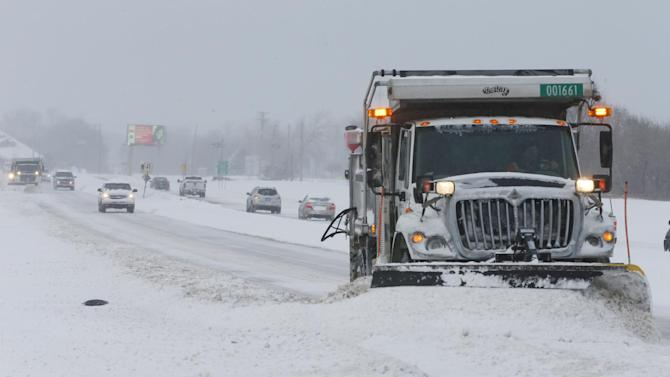 A city snow plow pusheds snow off of Zoo Blvd Thursday morning, Feb. 21, 2013 in Wichita, Kans. Kansas was the epicenter of the winter storm, with parts of Wichita buried under 13 inches of still-falling snow, but winter storm warnings stretched eastern Colorado through Illinois. (AP Photo/The Wichita Eagle, Bo Rader)