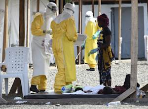 Health workers in protective suits treat a woman and…