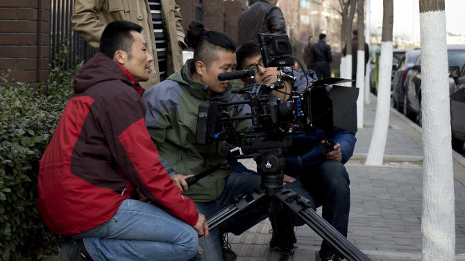 "In this Dec. 4, 2013 photo, Chinese director Sun Zhendong, left, and his crew prepare to film the ""Mr. Ball"" microfilm near a residential buildings in Changping, on the outskirts of Beijing. Microfilms, uploaded to Chinese YouTube-style and video-streaming sites, offer themes and subjects you won't come across in China's strictly censored cinemas. And thanks to video-capturing smartphones and basic editing software available on laptops, anyone can be a director these days. (AP Photo/Andy Wong)"