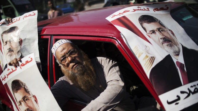 A supporter of Egypt's ousted President Mohammed Morsi holds a banner with Morsi's image, during a march against Egyptian Defense Minister Gen. Abdel-Fattah el-Sissi in the Nasr City section of Cairo on Friday, Aug. 2, 2013. (AP Photo/Manu Brabo)