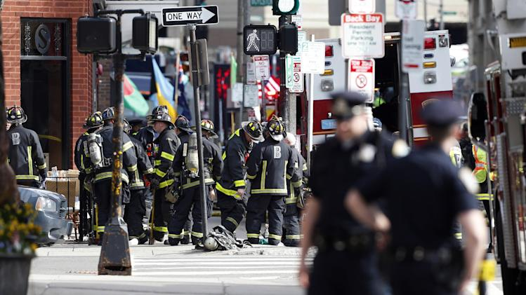 Firefighters gather one block from Boylston Street following an explosion at the finish line of the Boston Marathon in Boston, Monday, April 15, 2013.  Two bombs exploded at the Boston Marathon finish line Monday killing at least two people injuring dozens. (AP Photo/Michael Dwyer)