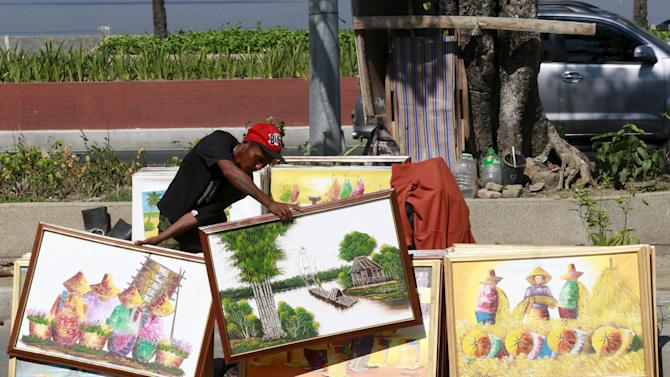Vendor displays some framed hand paintings he sells for PHP$2,500 ($56.00) each to attract buyers along a main road in Manila