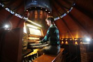Organist Christopher Keady plays the circular pipe organ at the Agnes Flanagan Chapel Tuesday, June 12, 2012, on the campus of Lewis & Clark College, in Portland, Ore. The Agnes Flanagan Chapel is a 16-sided architectural marvel that seats 650 under stained glass windows depicting the book of Genesis. In the early 1970s, it was also a big, conical quandary. Chapels aren't really chapels unless they have an organ, and the newly-minted structure at Portland's Lewis & Clark College was in need. (AP Photo/Rick Bowmer)